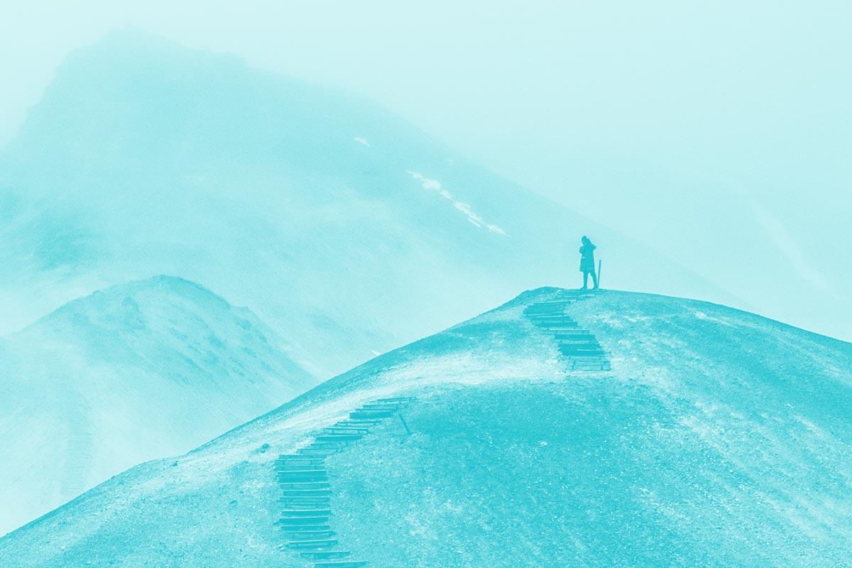 Fotografia de uma pessoa a escalar uma montanha alusiva ao conceito de conquista da acessibilidade
