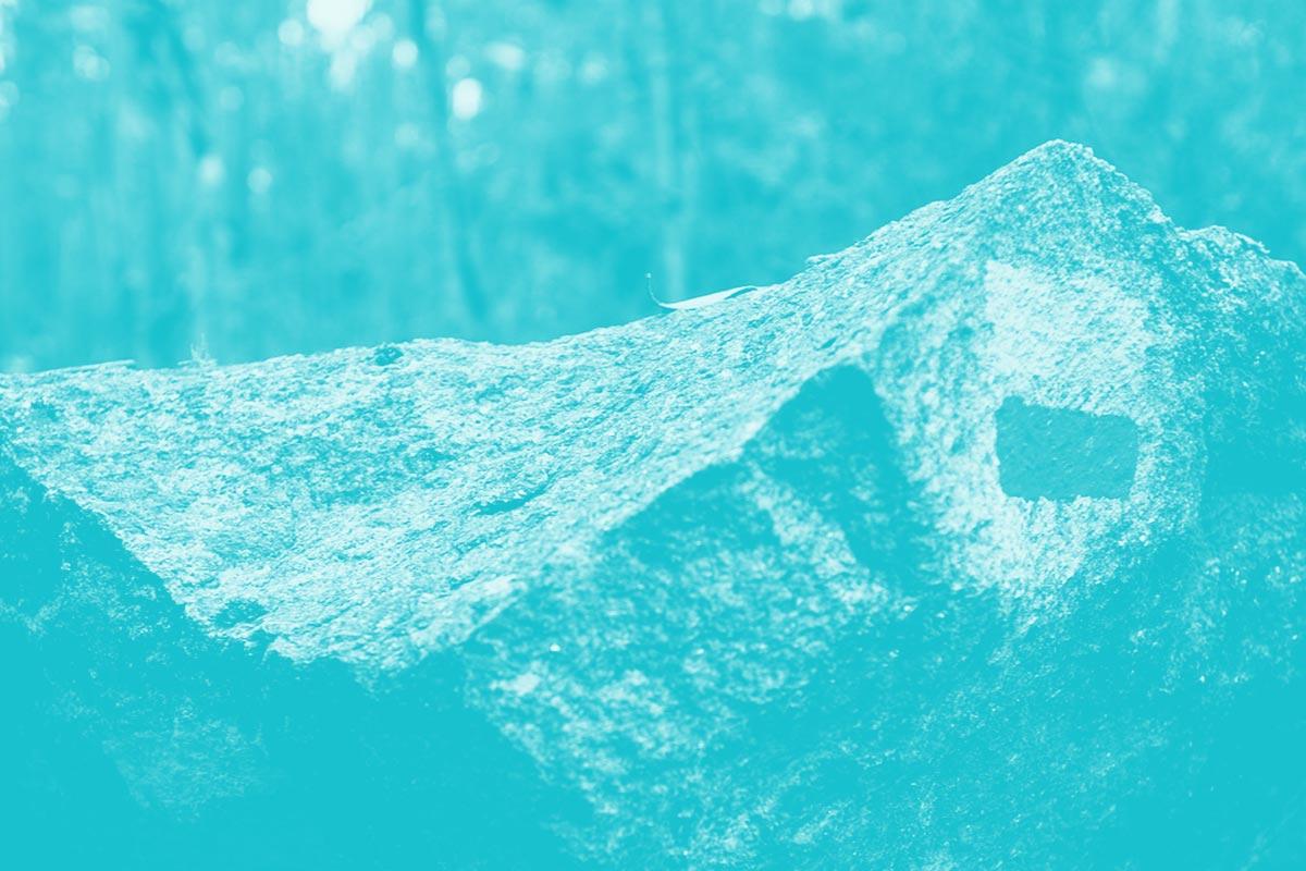 Fotografia de uma rocha no meio de uma paisagem de natureza com uma marca de um trilho alusiva do conceito de briefings