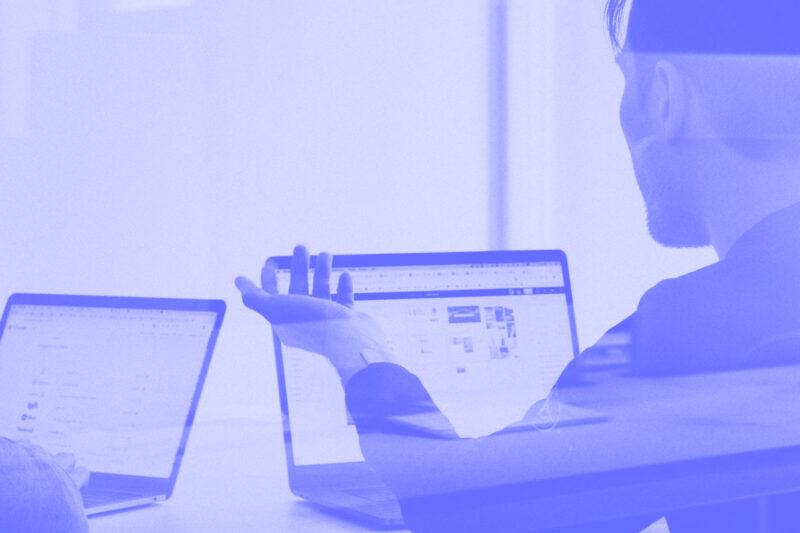 Fotografia de duas pessoas numa mesa e com computadores à frente a reunir alusiva ao conceito de reunião por video-chamada
