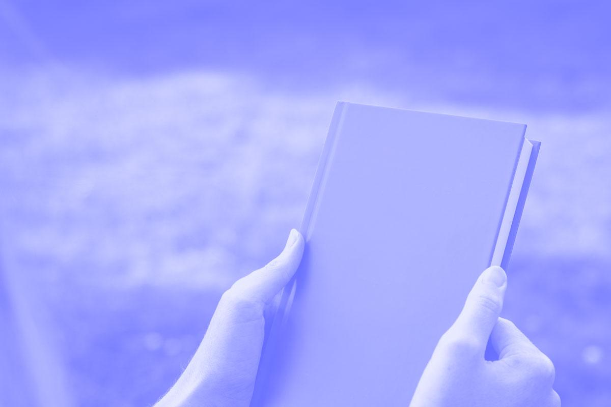 Fotografia de um livro na mão de uma pessoa alusiva aos conceitos de sugestões e referências
