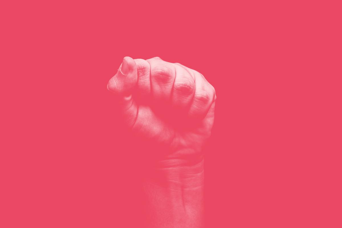Fotografia de uma mão fechada levantada ao alto em alusão ao conceito de democracia e participação