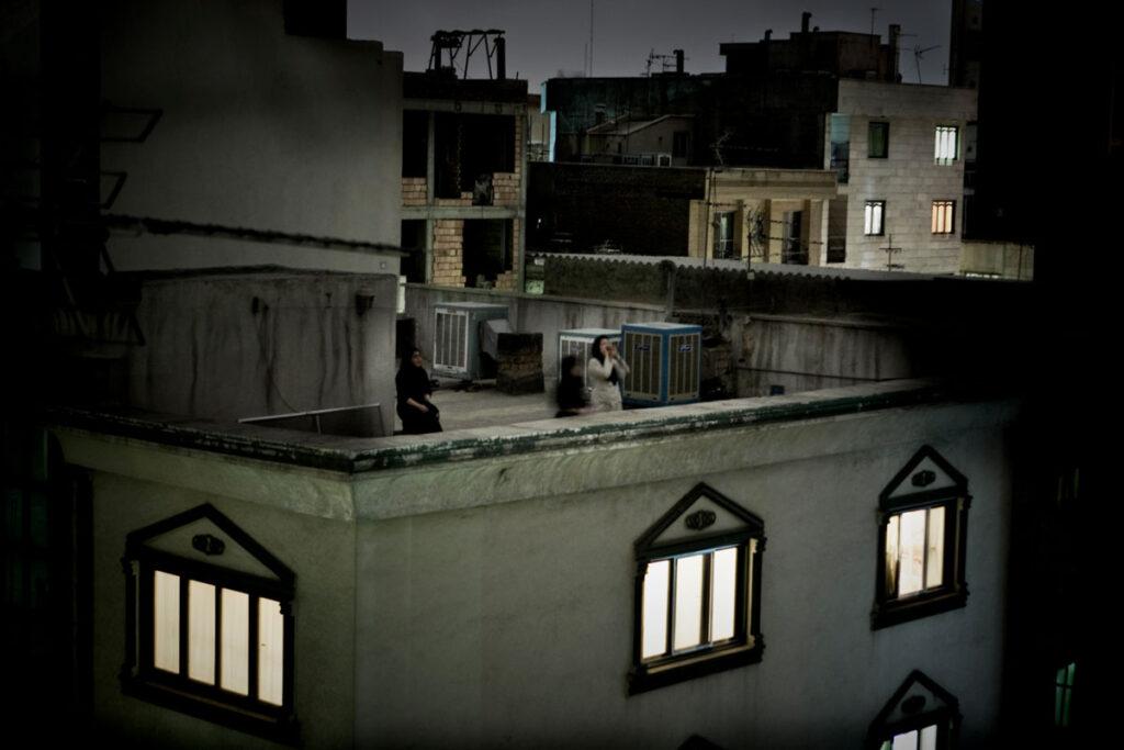 Fotografia de três mulheres a gritarem no topo de um telhado