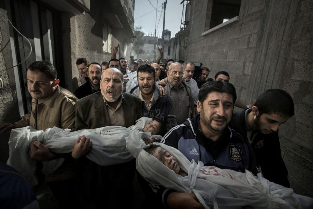 Fotografia de duas crianças mortas a serem transportadas por uma multidão