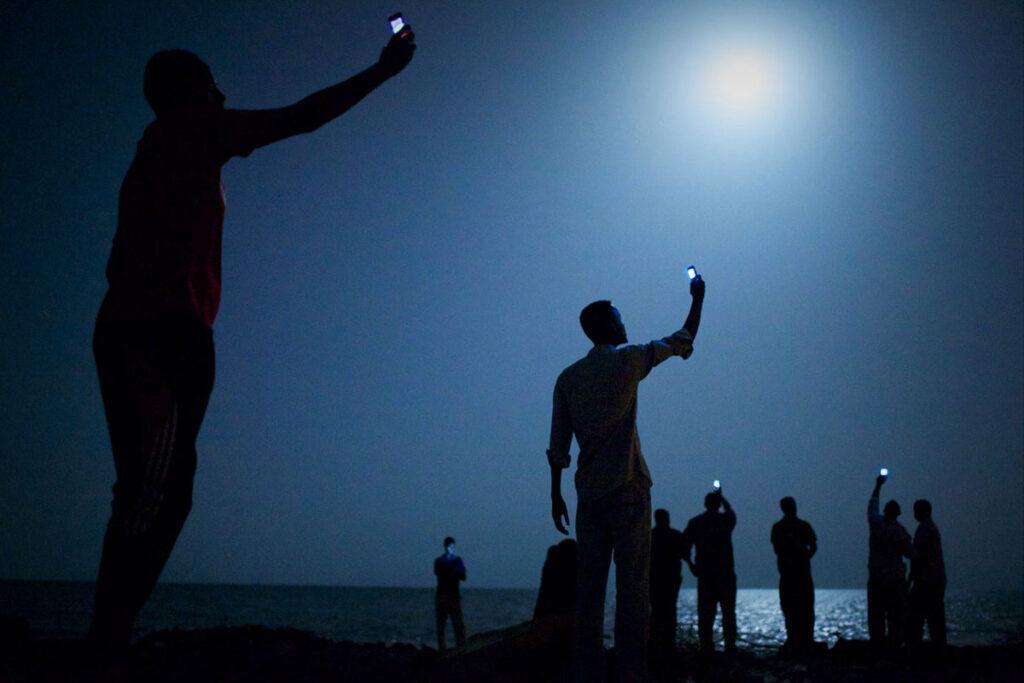 Fotografia de vários homens numa praia à noite de telemóveis no ar