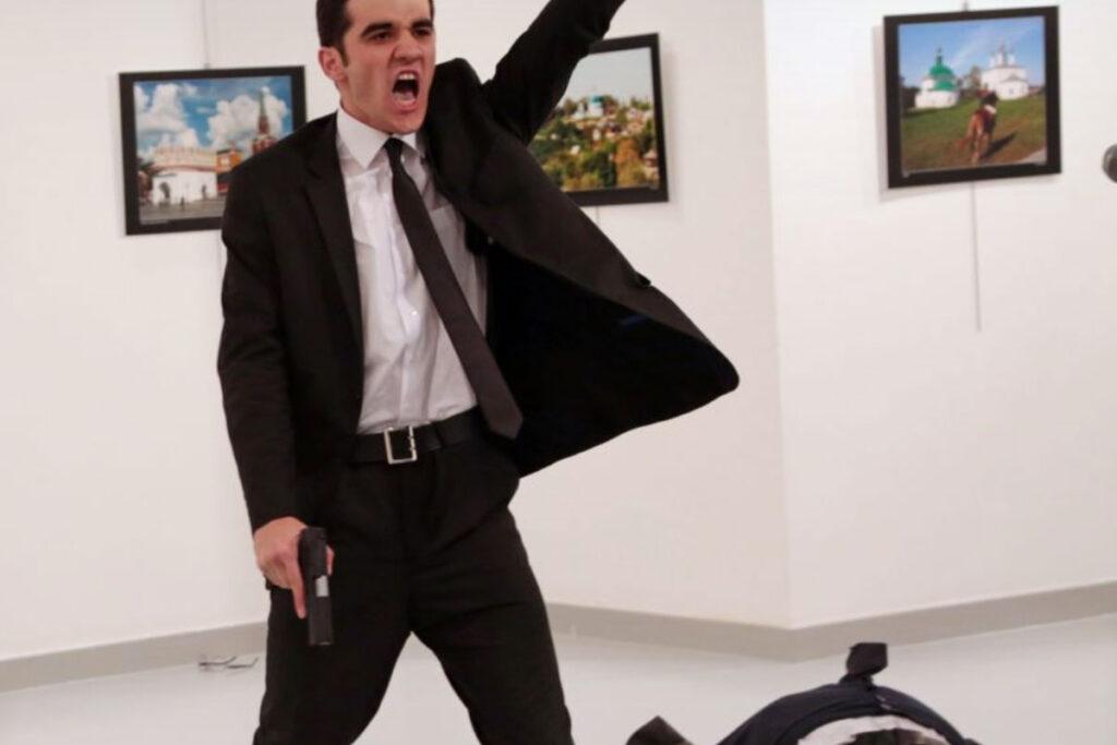 Fotografia de um homem com uma pistola na mão depois de matar outro homem