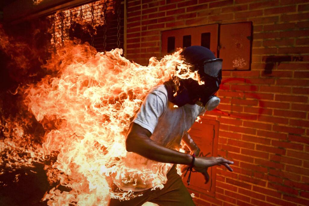 Fotografia de um homem em chamas a correr no meio da rua