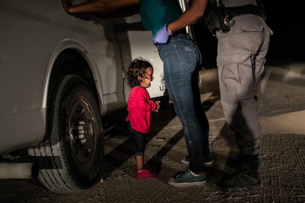 Fotografia de uma criança a chorar aos pés da mãe e de um polícia