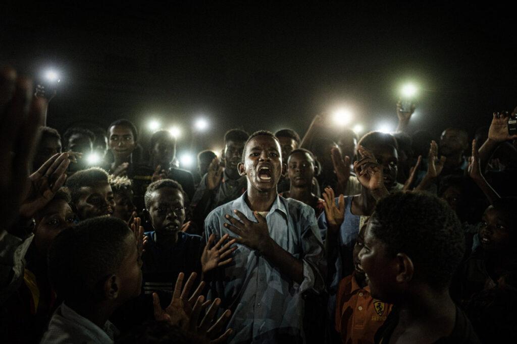 Fotografia de um homem a recitar poesia no meio da multidão às escuras