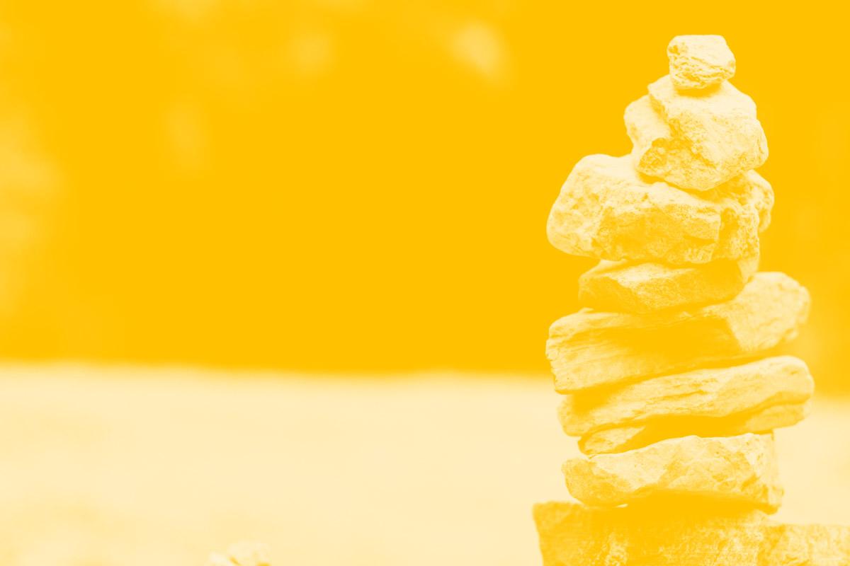Fotografia de algumas pedras em equilíbrio alusiva ao conceito de equilíbrio entre a vida familiar e profissional em teletrabalho