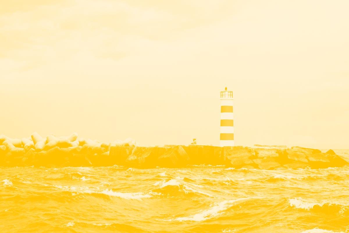 Fotografia de um farol à beira mar alusiva aos conceitos de observatório e acessibilidade